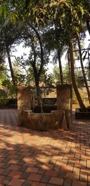 The well in the courtyard and the stick broom used to clean the courtyard lying against it